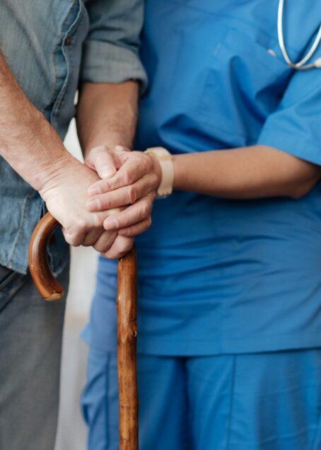 pasient med stokk og hjelpende sykepleier